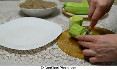 Woman prepares zucchini stuffed with meat - Woman prepares...