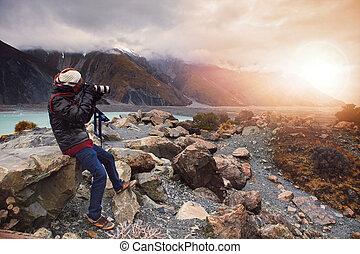 man take a photo on mountain cliff