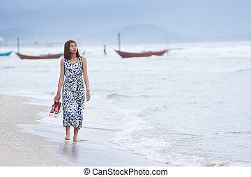 single woman walking lonely with sorrow face on sea beach
