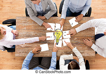 close up of business team with light bulb puzzle - business,...