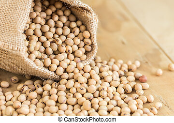 Soy beans in sack on wooden desk - Close up soy beans in...