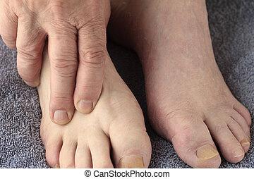 Man rubs aching foot