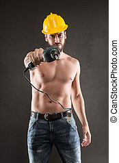 Portrait of attractive shirtless workman pointing with drill...