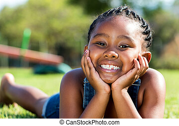 African girl laying with face on hands in park.