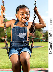 African girl sitting on swing in park - Close up portrait of...