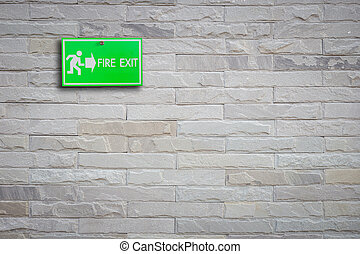 Green fire exit sign on stone wall background
