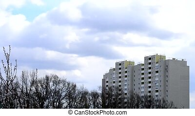 Time lapse of clouds moving above apartment block - Time...