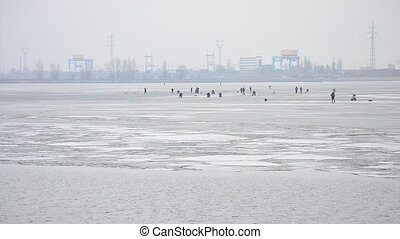 Fishermen angling on ice on background of electric power station
