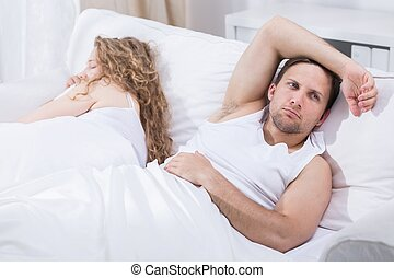 Thinking about future - Man is lying in bed with girlfriend...