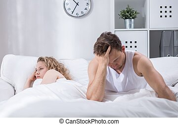Unhappy with each other - Couple is lying in bed upset after...