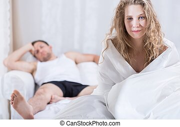 couple in bed - Young couple staying in bed after argument