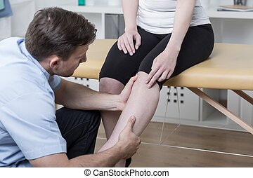 Patient with painful knee - Young physiotherapist diagnosing...