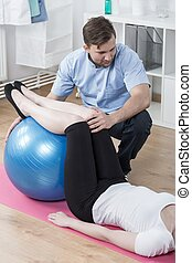 Working with exercise ball - Female patient is exercising...