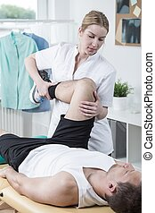 Man has painful knee - Young physiotherapist is training...