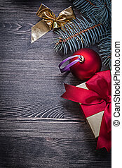 Christmas bauble bow pine twig present box on wood board