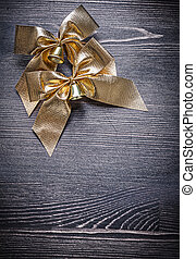 Christmas festal golden bows on wooden board holiday concept...