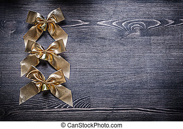 Christmas festal goldish bows on wooden board holiday...