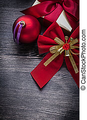 Christmas red ball bow gift box on wooden board