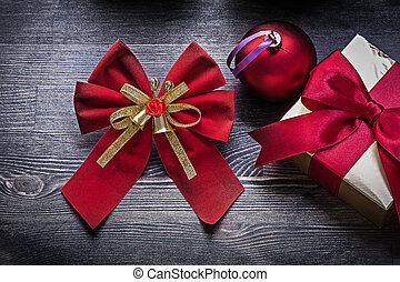 Christmas red ball bow present box on wooden board