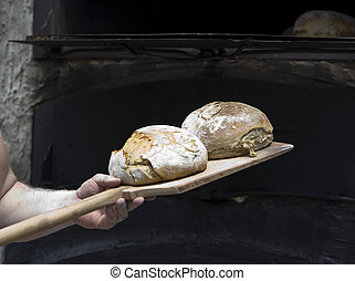 baker craft - traditional baker making bread with an old...