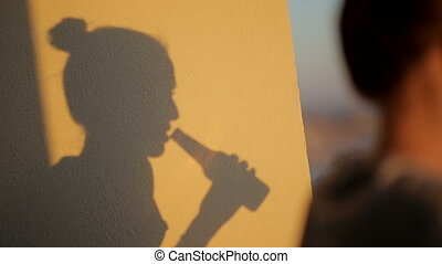 shadow silhouette of a woman drinking from beer bottle -...