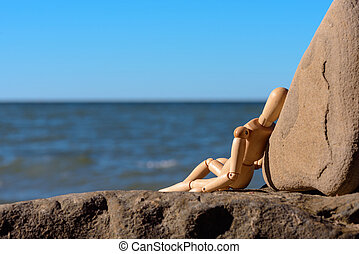 Relax on the beach - Wooden dummy sitting on the stony coast