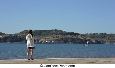Girl walking along the waterfront and looking at the sea,...
