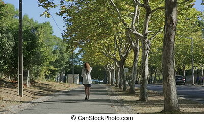 Girl walking throught cork tree alley street portugal...
