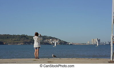 Girl takeing picture and looking at the river in portugal...