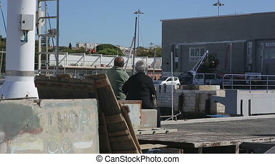 Old couple relaxing together at the fishboat harbor of...