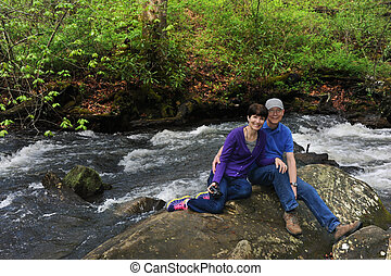 Adult Hiking - Young-at-heart couple rest on a boulder while...