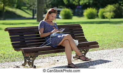 young girl sitting at the bench in a park and making notes -...