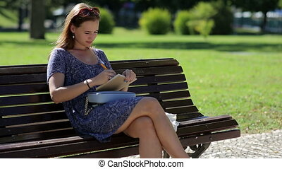 young girl sitting at the bench in a park and  drawing or making notes