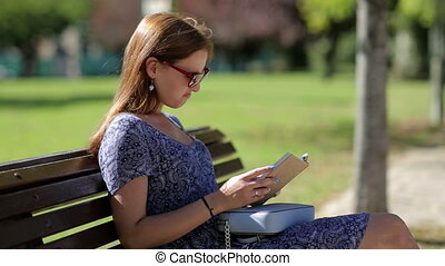 Young woman dislike reading a book and sitting on a bench...