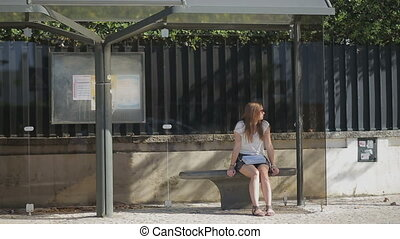 Lonely young girl waiting at bus stop in skirt, summertime -...