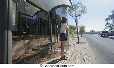 young girl waiting seating at bus stop with smart phone in...