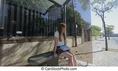Young woman waiting and talking by phone at glass bus stop...