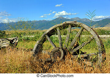 Bygone Era - Weathered and rusting wagon wheel sits...