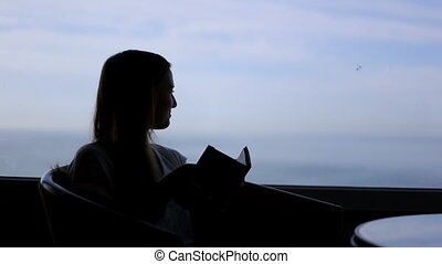 silhouette of young beautiful girl sits in a cafe with panoramic views of atlantic ocean. Reading a book, sightseing, thinking, enjoying the view
