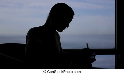 silhouette of young beautiful girl sits in a cafe with panoramic window sea view . Morning, with a book, notepad, wrighting, thinking