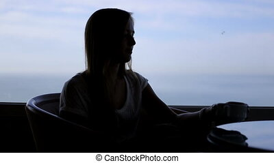 silhouette of young beautiful woman sits in a cafe with panoramic views of atlantic ocean. Morning with a cup of coffe, tea, drinking, thinking, beholding