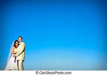 wedding couple against natural blue sky in the evening copy...