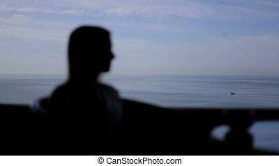 silhouette of young beautiful girl sits in a cafe with...