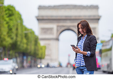 Beautiful woman holding a phone on the Champs Elysees in Paris