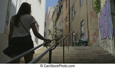 young woman goes up by ledder on street of Lisbon - ledder...