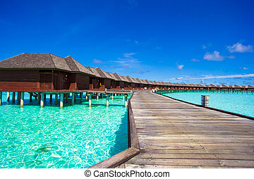 Water bungalows and wooden jetty on tropical island in...