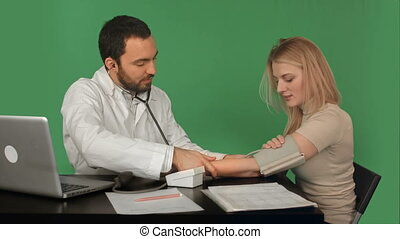 Doctor and patient with blood pressure meter in a hospital...