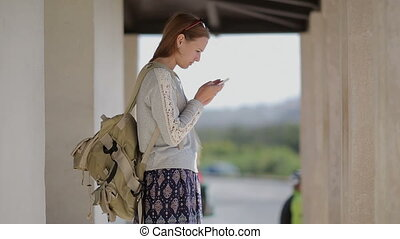 Young pretty girl tourist at the bus stop useing smartphone...