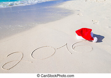 2016 and Merry Christmas written on beach white sand with...