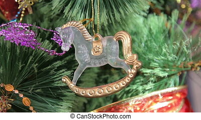 Decorations on green Christmas tree,toy horse - Toy horse on...